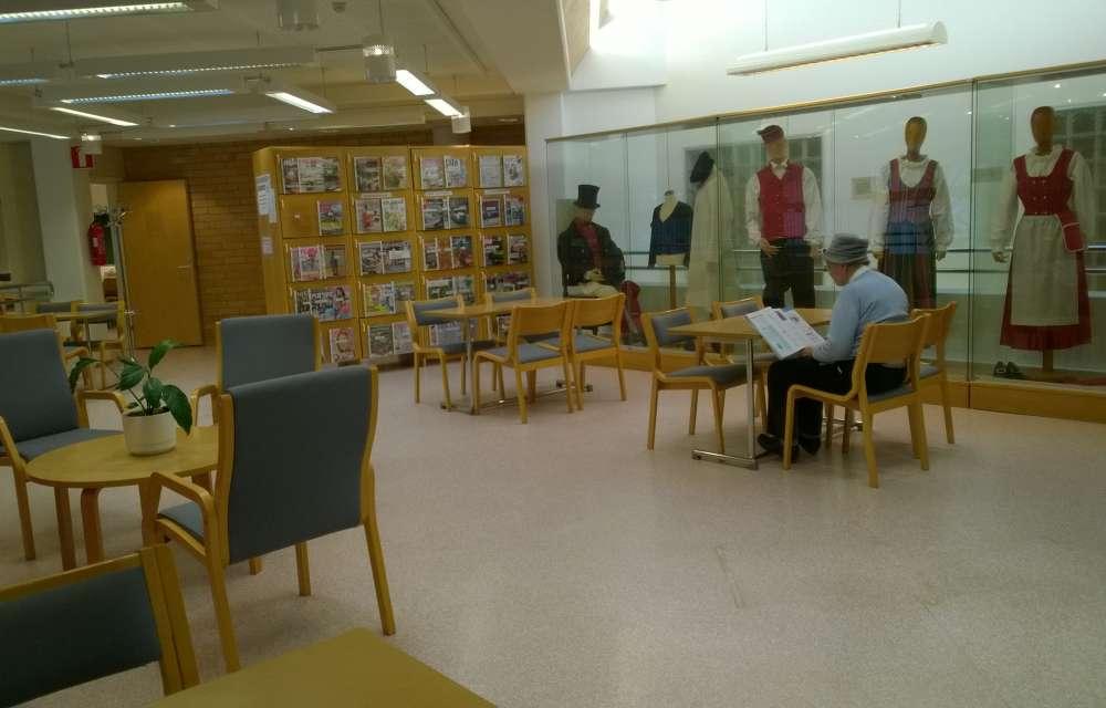 Kirjaston lukusalissa pöydän äärella luetaan lehteä