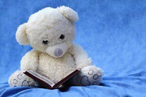 Valkoinen pehmonalle lukee kirjaa